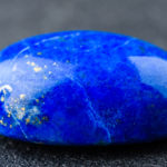 Rich blue lapis lazuli oval cabochon with small golden spots.